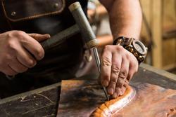 a blacksmith makes a piece of bronze