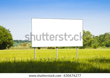 A blank advertising billboard in a grass field - image with copy space