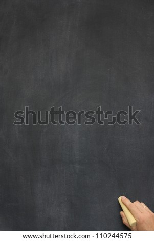 a blank blackboard / chalkboard with a hand holding chalk in the bottom right corner - stock photo