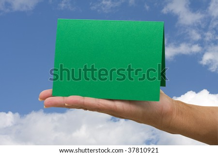 A blank card green card sitting in hands on a sky background, blank card - stock photo