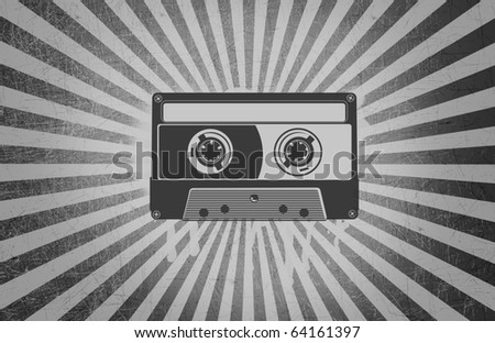 A blank cassette tape over a grey grunge background with light rays.
