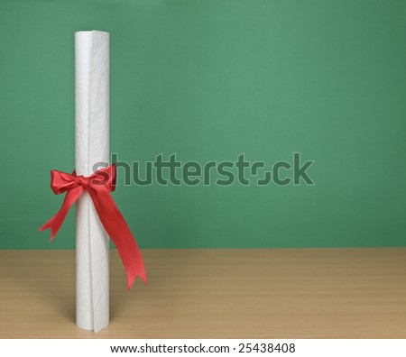 A blank chalkboard with a diploma on forefround.