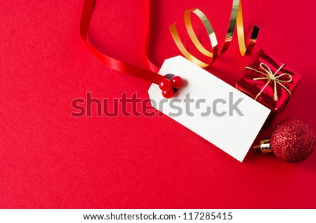 A blank Christmas gift tag, with red ribbon and artificial holly berries, on matte red background with shiny small gift box, glittery bauble, and gold foil spiral.  Copy space on tag and to it's left.