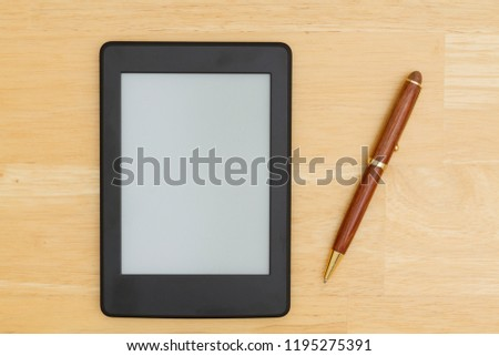 A blank e-ready on a desk with a pen that you can use as a mock up for your message #1195275391