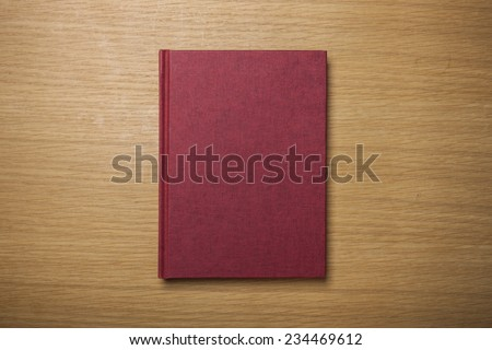 A blank(empty) red book(note, diary) cover on the wood desk(table), top view at the studio.