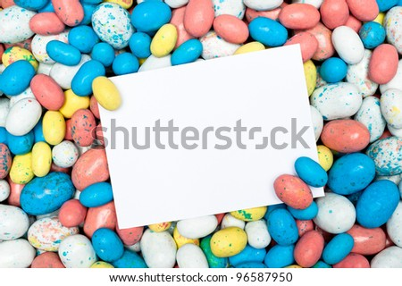 A blank message card in a pile of candy Easter eggs.