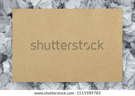 A blank piece of wood on a piece of paper to make a background texture.