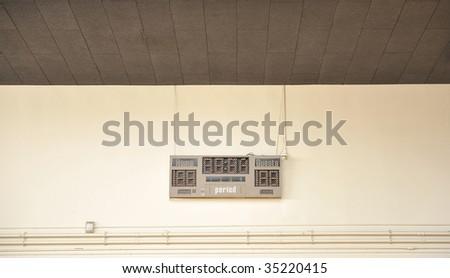 A blank scoreboard against a tan wall in an empty gym