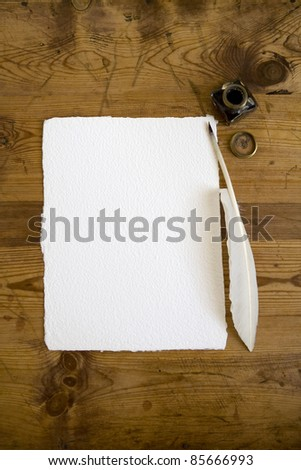 A blank sheet of handmade writing paper with quill pen and ink bottle ready to take type in the copy space.