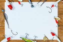A blank sheet of paper for your text on the topic of fishing. On a wooden table. The idea: how to catch, trophy, fish. Fishing gear, hooks and baits on a light wooden background.