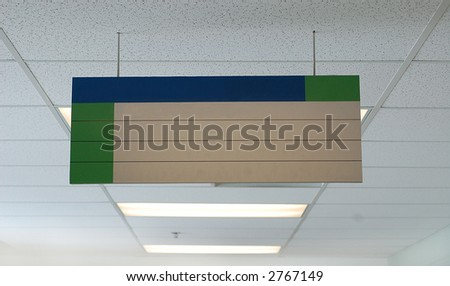 A blank sign hanging in a hallway of a school/office environment