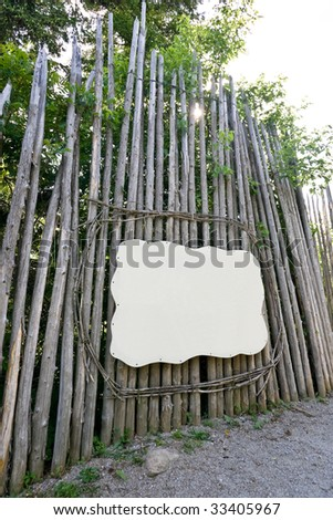 A blank sign / placard framed with wooden tree limbs, surrounded by logs, creating a long wall.