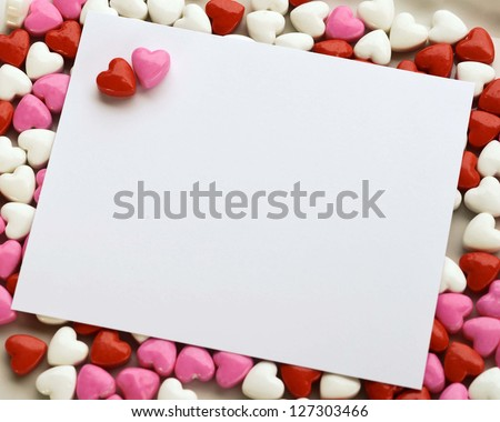 A blank white note card surrounded by heart candy
