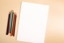 A blank white sheet and colored pencils for drawing on a plain textured background with space for copying and lettering.