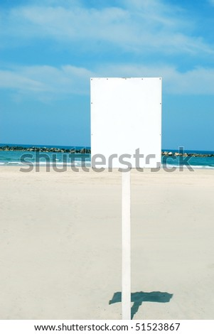 A Blank white Sign on a pole by the Sea side