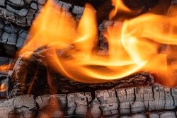 A blazing fire in the dark. Ignition of wood in the fire. A bright burning flame. Sparks and flames in the dark. Incandescent heat and coals and flames.A blazing bonfire.