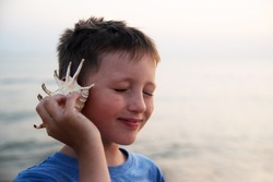 A blind boy listens to the sound of the sea, leaning a seashell against his ear.