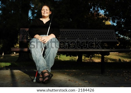 A blind woman enjoys the afternoon sun in a park