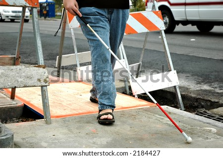 A blind woman navigates through construction on a sidewalk