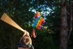 A blindfolded boy hitting a pinata with a stick