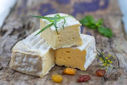 A block of Pont-l eveque French Normandy cheese resting on wooden backgrond