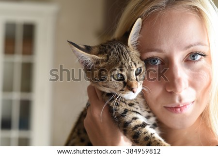 A blond blue-eyed girl with exclusive savannah A1 or Asher cat in studio with baroque style
