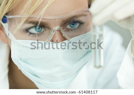A blond blue eyed woman doctor or female medical scientific researcher looking at a test tube of clear solution in a laboratory