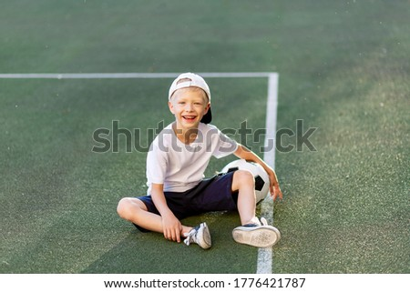 a blond boy in a cap in a sports uniform sits on a football field with a soccer ball, sports section. Training of children, children's leisure.