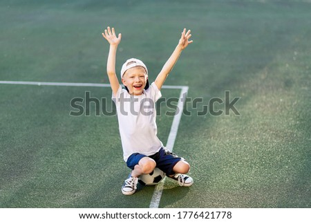 a blond boy in a cap in a sports uniform sits on a soccer ball on the football field and shouts Goal, sports section. Training of children, children's leisure.