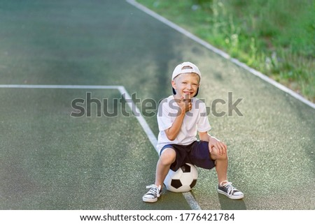 a blond boy in a cap in a sports uniform sits on a soccer ball on the football field, sports section. Training of children, children's leisure.