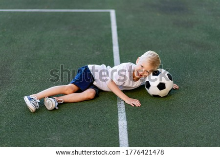 a blond boy in a sports uniform is lying on the football field with a soccer ball, sports section. Training of children, children's leisure
