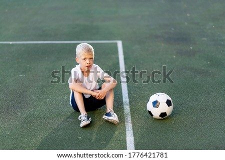 a blond boy in a sports uniform sits on a football field with a soccer ball, sports section. Training of children, children's leisure.