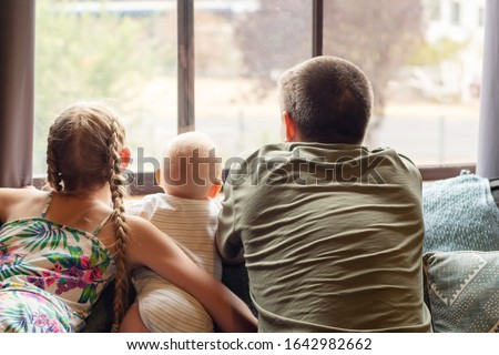 A blond girl, her baby brotherand their father looking through the window. Family concept