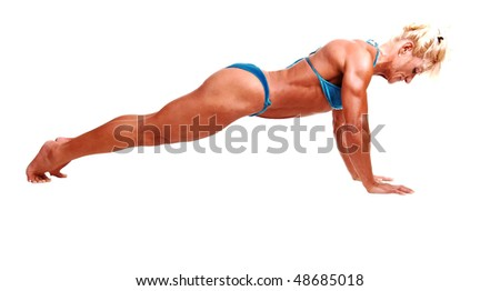 A blond muscular bodybuilding girl doing push ups in the studio shooing her  strong legs and the upper body and arms, over white background.