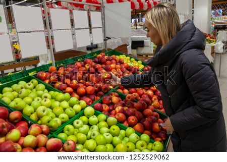 A blond woman in a supermarket buys apples from the beautifully laid out rows on the shelves, stopping her choice on red, holds it in her hand.