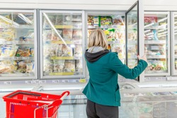 A blond woman picking frozen goods from a supermarket refridgerator with a red shopping cart next to her. Casual shopping.