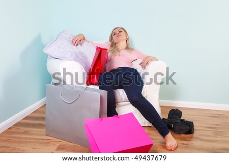 A blond woman slumped in an armchair exhausted after a shopping trip.