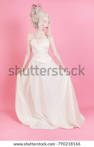 bccb7900230 A blond woman with a beautiful luxurious rococo hair style in a white dress  on a