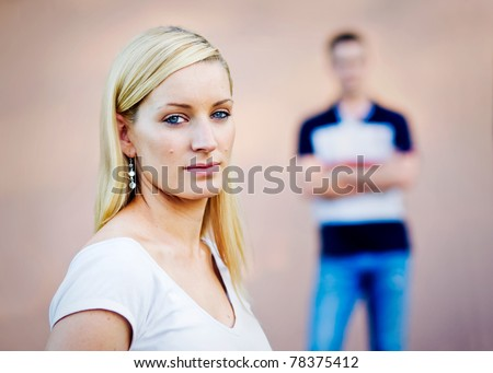 A blond young adult girl who with a serious and somewhat angry look on her face.  Her boyfriend is behind her with his arms crossed - selective focus is used so his expression cannot be seen.