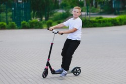 a blonde boy in a white T-shirt and black pants riding a scooter. High quality photo