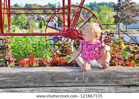 A blonde, curly haired toddler girl, digging in  the dirt of a raised flower bed in a public park garden bed.