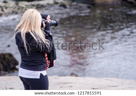 A blonde female photographer uses her DSLR camera to work the scene at the Atlantic Ocean shoreline
