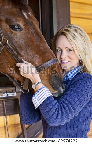 A blonde female with horses in an equestrian environment
