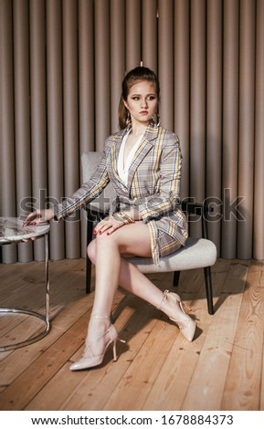 a blonde girl in a beige yellow checked suit with a skirt in high heels with her hair in a ponytail poses  sitting on a chair in a beige interior in a photo Studio in an apartment at home stock photo