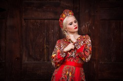 A blonde girl in the national Russian red dress and headdress kokoshnik leaning against a wooden wall of the house and braiding her hair. Russian national clothes. Early spring time