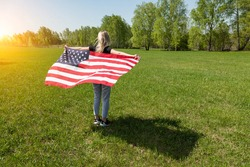 A blonde girl with flying hair holds an American flag behind her back in the sun in the afternoon in a field with green grass and trees. Freedom and Independence Day celebration in the hot summer July
