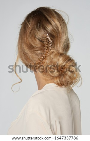 A blonde lady with messy hair bun is wearing a creamy blouse and posing with her back to the camera. The lady's hairdo is decorated with a metal hair pin made as a crown of golden embossed leaves.