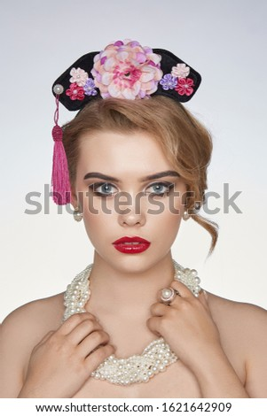 A blonde lady with naked shoulders is wearing a wide pearl necklace. The girl's hairdo is decorated with a black headband made as a crest with pink and lilac flowers, pearls and a pink tassel.