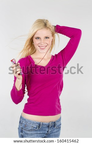A blonde model enjoying music on an mp3 player
