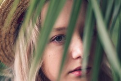 A blonde teenage girl in a straw hat looks at the camera from behind a palm leaf.Concept of closeness to nature.Urban jungle,fashion concept.Close-up,selective focus.